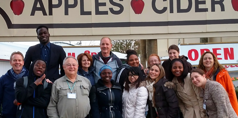 Group in front of apple cider sign